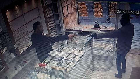 Dükkanını soymaya çalışan hırsıza silahıyla karşılık verdi