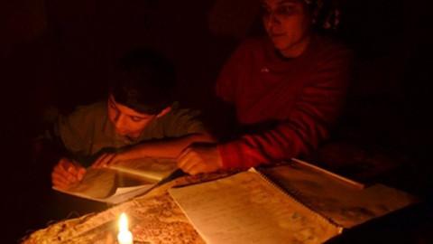 3 çocuk ödevlerini mum ışığında yapıyor